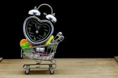 Alarm clock with school supplies on shopping cart , black backgr Stock Photos