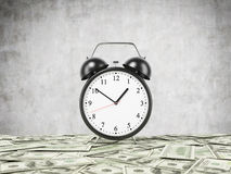 An alarm clock is settled on the surface which is covered by dollar notes. Concrete background. Royalty Free Stock Images