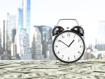 An alarm clock is settled on the surface which is covered by dollar notes. Stock Photos