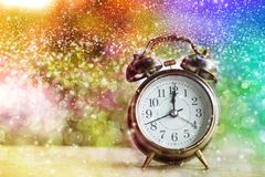 Alarm clock showing midnight on New Year or Christmas day with colorful abstract bokeh. Glitter light and snow effect background for festive and celebration stock photo