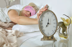 Alarm Clock Showing 7.00 am. Silver clock showing seven o`clock in the morning with a hand of a awake woman on it Stock Photos