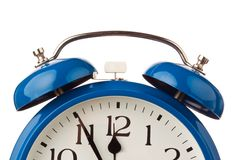 Alarm clock shows five before twelve. Stock Photo