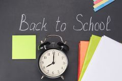 He alarm clock shows the time eight hours against the background of the chalk board and school subjects, it`s time to go to schoo. L royalty free stock photography