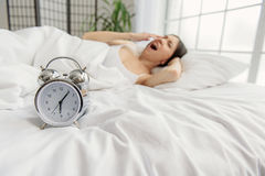 Alarm clock situating near woman. What time is it. Snooze locating in front of yawing female Royalty Free Stock Image