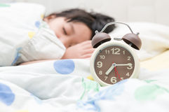 Alarm clock and sleep child. Alarm clock and girl sleep on background Stock Photo