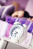 Alarm clock with a sleeping young woman Royalty Free Stock Photo
