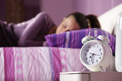An alarm clock with a sleeping young woman Stock Photos