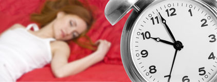 Alarm clock and sleeping young woman Stock Photography