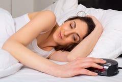 Alarm clock. Sleepy young woman switching off the alarm clock stock image