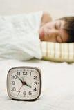 Alarm-clock and sleepyhead Stock Photos