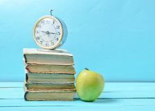 Alarm clock on stack of old books, apple on a blue background. School concept, education.  royalty free stock photo