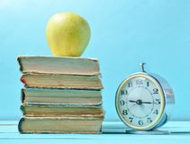 Alarm clock, stack old books, apple on a blue background. School concept, education.  royalty free stock image