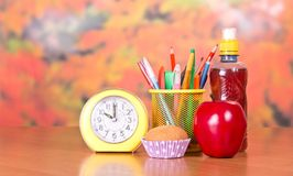Alarm clock, stand with pencils, cake Royalty Free Stock Images