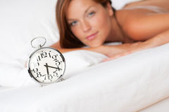Alarm clock standing on bed, woman in background Royalty Free Stock Photo