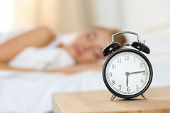 Alarm clock standing on bedside table going to ring early mornin Royalty Free Stock Photography