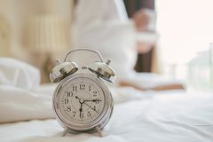 Alarm clock standing on bedside table has already rung early morning to wake up woman is stretching in bed in. Background.Relaxing concept royalty free stock images