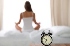 Alarm clock standing on bedside table has already rung early morning to wake up woman in bed sitting in background Royalty Free Stock Photos