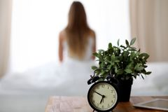 Alarm clock standing on bedside table has already rung early morning to wake up woman in bed sitting in background. Early awakening, not getting enough sleep Royalty Free Stock Images