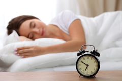 Alarm clock standing on bedside table has already rung early morning to wake up woman in bed sleeping in background Stock Image