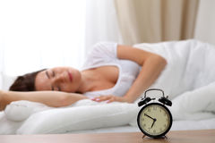 Alarm clock standing on bedside table has already rung early morning to wake up woman in bed sleeping in background Royalty Free Stock Photo