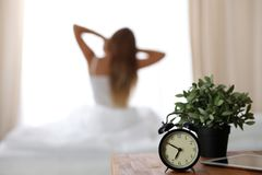Alarm clock standing on bedside table has already rung early morning to wake up woman is stretching in bed in background. Early awakening, not getting enough Royalty Free Stock Image