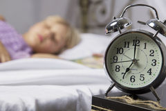 Alarm clock standing on bedside table. Wake up of an asleep young girl stopping alarm clock on a bed in the morning.  Royalty Free Stock Photography