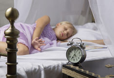 Alarm clock standing on bedside table. Wake up of an asleep young girl stopping alarm clock on a bed in the morning.  Stock Photography
