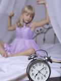 Alarm clock standing on bedside table. Wake up of an asleep young girl is stretching in bed in background.  Royalty Free Stock Photography