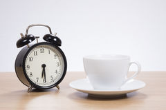 Alarm clock standing by coffee cup. On wooden table against white background Royalty Free Stock Photo