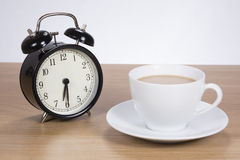 Alarm clock standing by cup of coffee Stock Photo