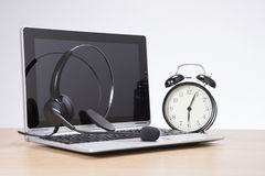 Alarm clock standing by laptop with headset Royalty Free Stock Photography
