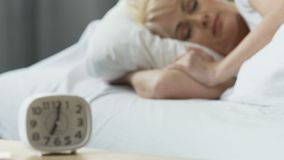 Alarm clock standing on nightstand, woman sleeping in bed, comfort at home. Stock footage stock video footage