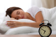 Free Alarm Clock Standing On Bedside Table Has Already Rung Early Morning To Wake Up Woman In Bed Sleeping In Background Royalty Free Stock Photo - 94561465