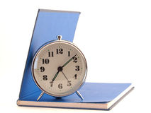 The alarm clock standing on the open book Royalty Free Stock Photography