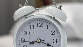 Alarm clock standing on table and ringing, time for awakening, deadline urgency. Stock footage stock footage