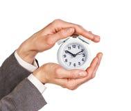 Alarm clock stands on the human palm Stock Photos