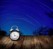 Star trails, Long exposure concept. Alarm clock with star trails background. Long exposure concept Stock Photo