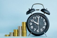 Alarm clock and step of coins stacks, time for savings money con Royalty Free Stock Photo