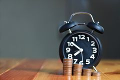 Alarm clock and step of coins stacks on working table, time for Stock Photography