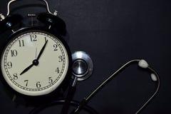 Alarm clock, stethoscope on black background royalty free stock photo