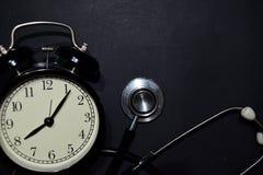 Alarm clock, stethoscope on black background royalty free stock images