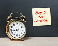 Alarm clock and sticker with text back to school on the chalkboa Stock Photo