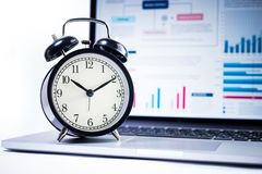 Alarm clock with stock graph chart in laptop screen background. Royalty Free Stock Image