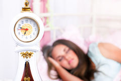 Alarm clock. And a student sleeping in the background Royalty Free Stock Photography