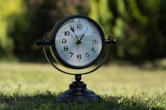 Alarm clock in sunlit spring garden.  Stock Image