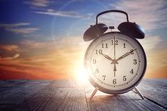 Alarm clock at sunset stock photo