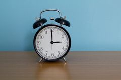 Alarm clock on table with blue background Stock Photo