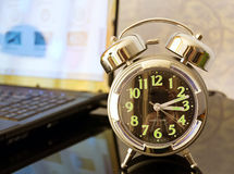 Alarm clock. Is on the table in front of a laptop Royalty Free Stock Image