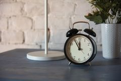 Alarm clock with table lamp and flower in pot on nightstand Royalty Free Stock Photo