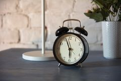 Alarm clock with table lamp and flower in pot on nightstand Stock Image